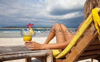 Woman with a cocktail on beach