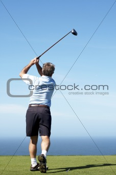 Senior male golfer playing off the tee box