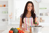 Gorgeous woman preparing vegetables while standing