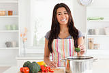 Beautiful woman preparing vegetables while standing