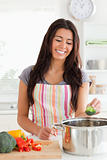 Good looking woman preparing vegetables while standing