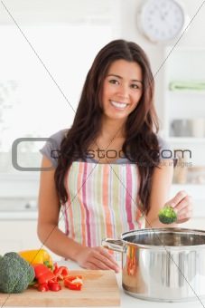 Charming woman preparing vegetables while standing