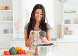 Lovely woman preparing vegetables while standing