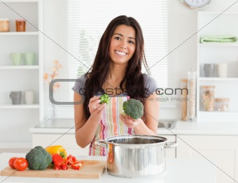 Gorgeous female preparing vegetables while standing