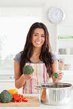 Attractive female preparing vegetables while standing