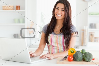 Beautiful woman relaxing with her laptop while standing