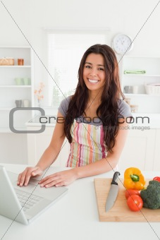 Charming woman relaxing with her laptop while standing