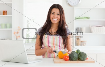 Beautiful woman relaxing with her laptop while cooking vegetables