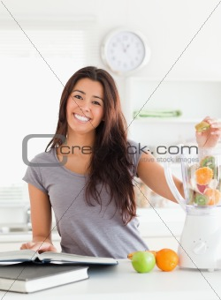 Good looking woman consulting a notebook while filling a blender