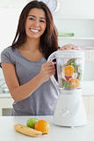 Good looking woman using a blender while standing