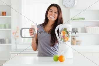 Beautiful woman using a blender while holding a drink