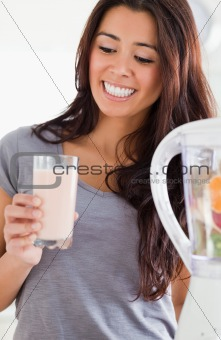 Pretty woman using a blender while holding a drink