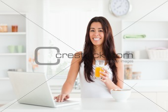 Beautiful woman relaxing with her laptop while holding a glass