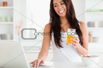 Charming woman relaxing with her laptop while holding a glass