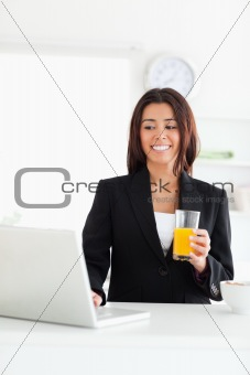 Attractive woman in suit relaxing with her laptop