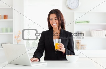 Charming woman in suit relaxing with her laptop