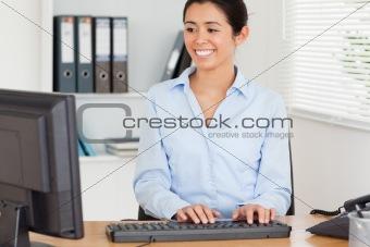 Beautiful woman typing on a keyboard while sitting