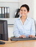 Good looking woman typing on a keyboard while sitting