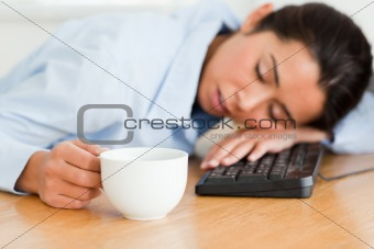 Beautiful woman sleeping on a keyboard while holding a cup