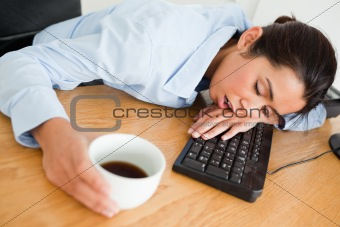 Attractive woman sleeping on a keyboard while holding a cup