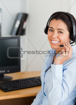 Attractive woman wearing a headset and discussing while sitting