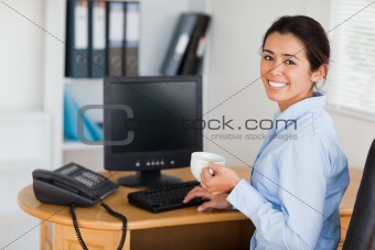Attractive woman holding a cup of coffee while sitting