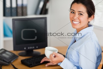 Beautiful woman holding a cup of coffee while sitting