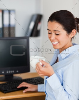 Charming woman holding a cup of coffee while sitting