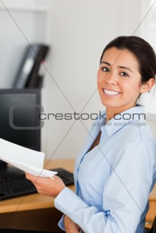 Beautiful woman holding a sheet of paper and posing while sittin