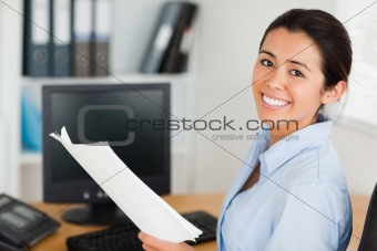 Attractive woman holding a sheet of paper and posing while sitting