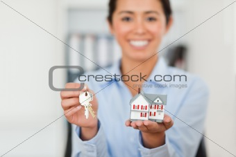 Attractive woman holding keys and a miniature house