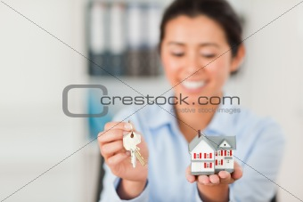 Charming woman holding keys and a miniature house while looking