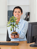 Beautiful woman holding a plant while looking at the camera