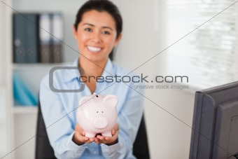Attractive woman holding a piggy bank while looking at the camera