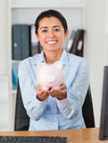 Good looking woman holding a piggy bank while looking at the camera