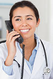 Beautiful female doctor on the phone and posing