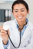 Pretty female doctor using a stethoscope while looking at the ca
