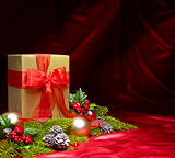 Present decorated with red satin and Christmas decoration
