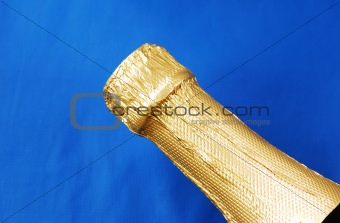 Close up view of a champagne bottle isolated on blue