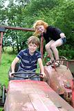 Two children playing on an old tractor