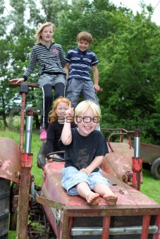 Four children playing on an old tractor