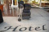 Suitcases and trolley in front of hotel