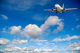 Air travel - Plane flying in blue sky with clouds