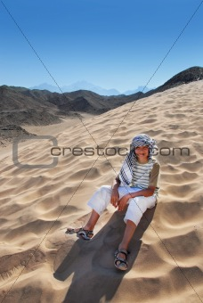 Boy sitting on sand dune in Egypt