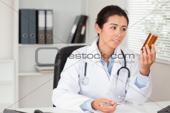 Attractive pensive doctor holding a box of pills