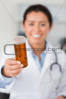 Portrait of an attractive smiling doctor holding a box of pill