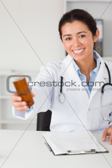 Beautiful smiling doctor holding a box of pills while sitting