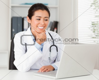Attractive female doctor working with her laptop while sitting