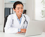 Good looking female doctor working with her laptop while sitting