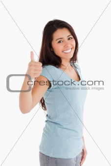 Beautiful woman having her thumb up while standing